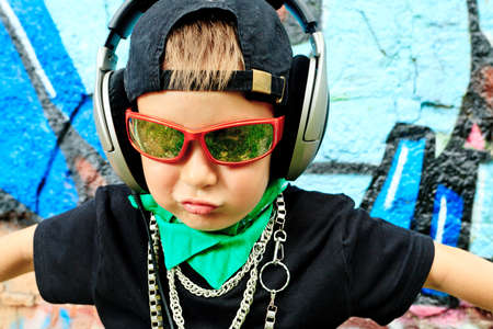 Portrait of a trendy little boy  with headphones outdoors. photo
