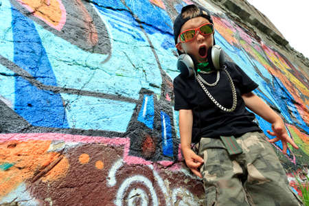 street dance: Portrait of a trendy little boy  with headphones outdoors.
