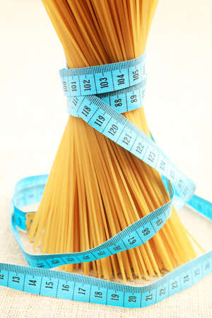 Food concept: bunch of uncooked spaghetti tied with tape measure. photo