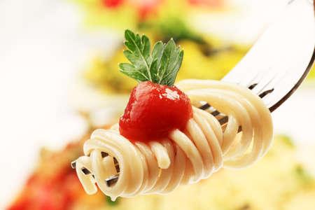 Primer plano de un tenedor con espagueti sobre platos de pasta.