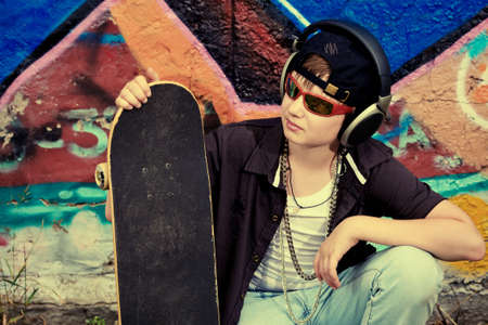cool boy: Portrait of a trendy boy teenager with headphones and skateboard outdoors.