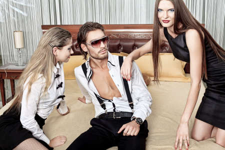 Portrait of a handsome fashionable man with two charming women posing in the interior. Stock Photo