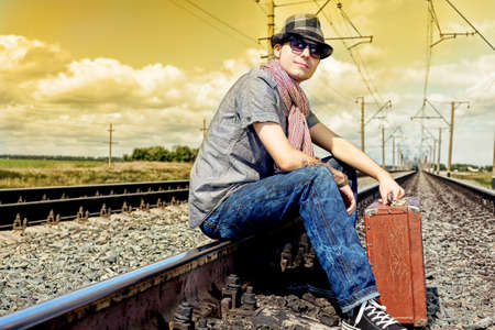 Portrait of a handsome young man posing at a railroad. photo