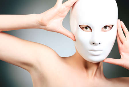 Shot of a woman in white mask over grey background.