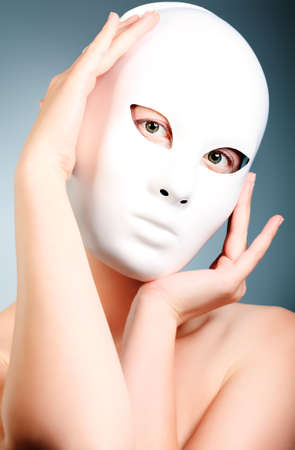 anonym: Shot of a woman in white mask over grey background.