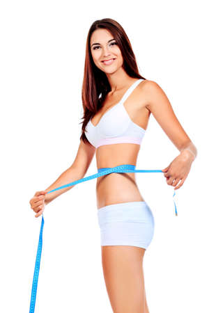perfect fit: Slender woman measuring her waist. Diet, healthy lifestyle. Stock Photo