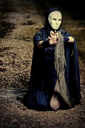 Shot of a woman in mask wearing old-fashioned black dress.  photo