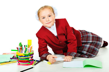 Portrait of a cute schoolgirl with pencils and crayons. Isolated over white background. photo