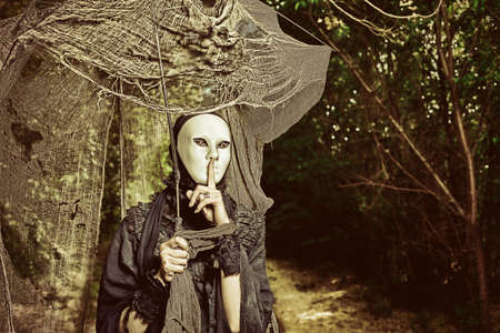 Shot of a sad woman in mask wearing old-fashioned  black dress.  photo