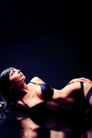 erotic nude women: Shot of a sexy woman in black lingerie over black background. Stock Photo