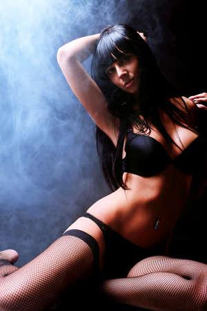 sexy girl nue: Tir d'une femme sexy en lingerie noire sur fond sombre avec de la fum�e.