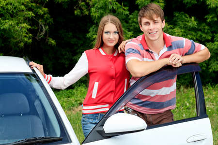 Happy young couple having summer trip on a car. photo