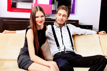 gangster girl: Portrait of a handsome fashionable man with  charming woman posing in the interior. Stock Photo