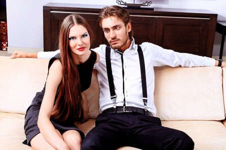 Portrait of a handsome fashionable man with  charming woman posing in the interior. photo
