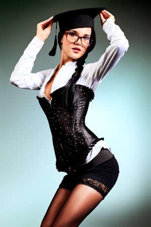 corsetto: Sexy giovane donna in occhiali posa su sfondo grigio.