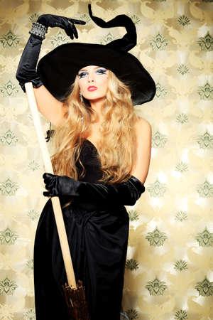 escoba: Encantadora bruja de halloween con escoba sobre fondo vintage. Foto de archivo