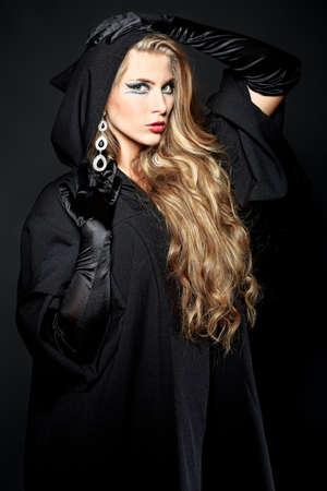 evil girl: Charme strega halloween su sfondo nero. Archivio Fotografico