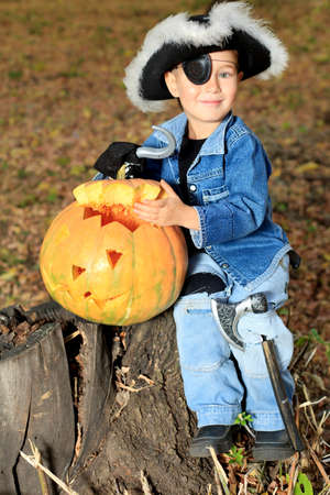Shot of a little boy in pirate costume posing with halloween pumpkin outdoor. photo