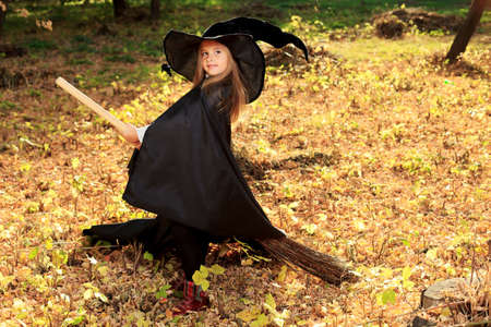 Shot of a little girl in halloween costume posing with broom and pumpkin outdoor.