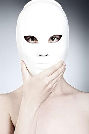 Aufnahme einer Frau in weißen Maske über grauem Hintergrund.