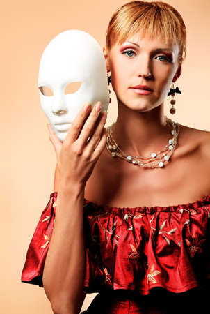 theater mask: Portrait of a beautiful woman in medieval era dress. Shot in a studio. Stock Photo