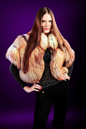 Portrait of a beautiful young woman in a fur over black background. photo