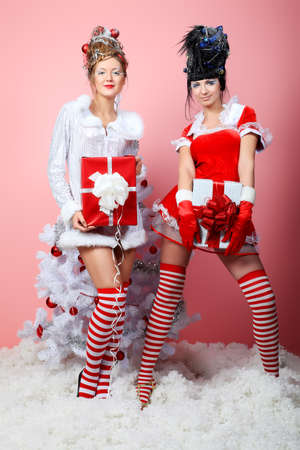 Two beautiful young women in Christmas clothes posing with New Year tree.