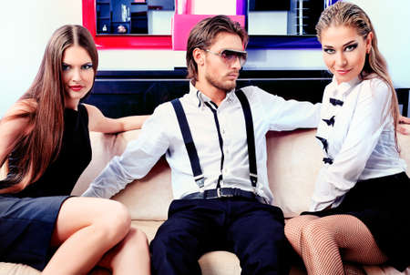 bed clothes: Portrait of a handsome fashionable man with two charming women posing in the interior. Stock Photo