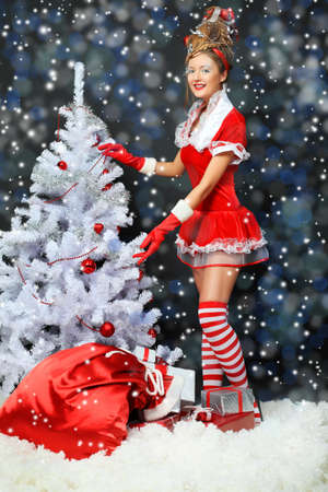 Fashionable young woman in Santa Claus clothes with presents over black background. Stock Photo - 10834975