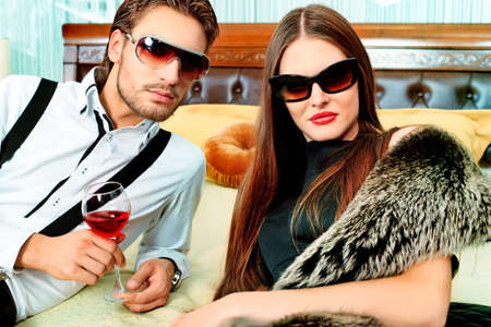 fashionable sunglasses: Portrait of a handsome fashionable man with  charming woman posing in the interior. Stock Photo
