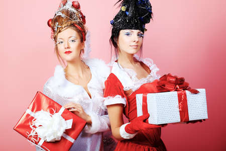 Two beautiful young women in Christmas clothes posing over pink background. photo