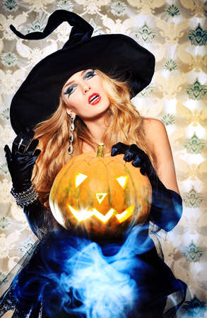 traditional costume: Charming halloween witch over vintage background.