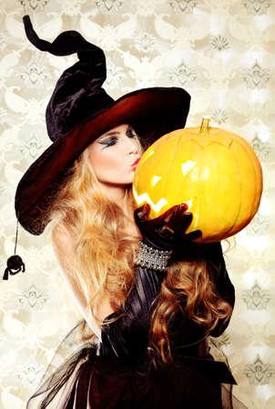 bruja: Encantadora bruja de halloween sobre fondo vintage. Foto de archivo