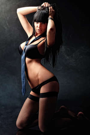 nude fashion model: Shot of a sexy woman in black lingerie over black background. Stock Photo