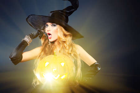 黒の背景上の魅力的なハロウィーンの魔女。