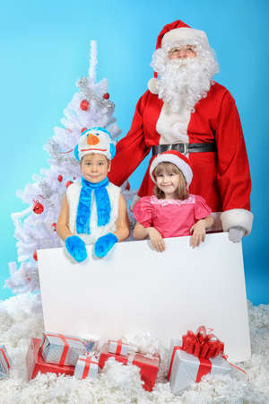 Christmas theme: Santa Claus and little children holding white board.  photo