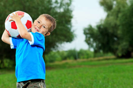 Shot of a cute laughing boy with a ball outdoor. photo