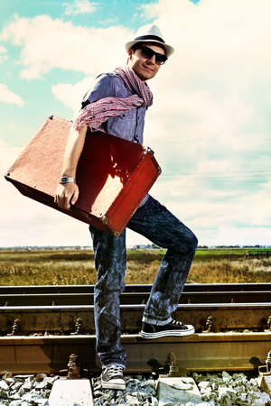 suitcases: Handsome young man walking along railroad. Stock Photo