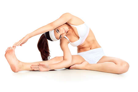 Shot of a sporty young woman doing yoga exercise. Isolated over white background. photo