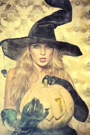 Charming halloween witch over vintage background. photo