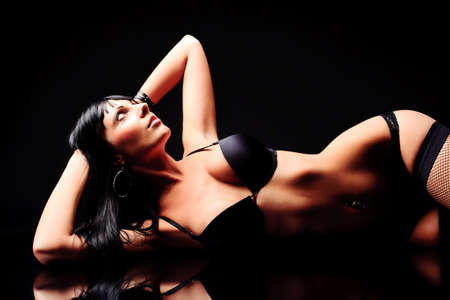nude black women: Shot of a sexy woman in black lingerie over black background. Stock Photo