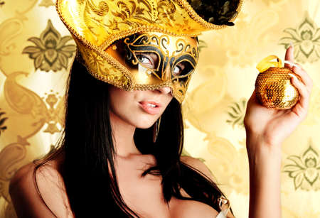 Shot of a sexy woman in a mask over vintage background. Stock Photo - 10922697