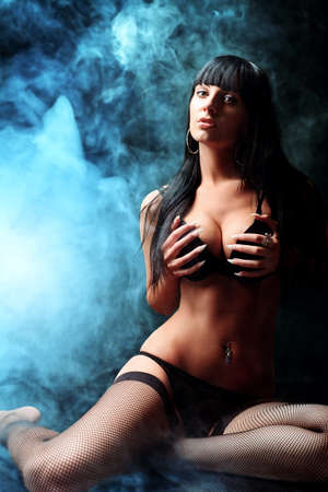 Shot of a sexy woman in black lingerie over dark background with smoke. Stock Photo - 10922713