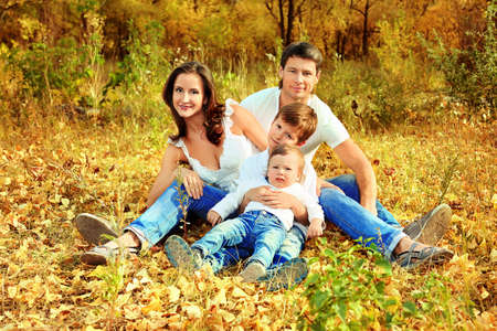 Happy family having a rest outdoor in the autumn park. Stock Photo - 10930960