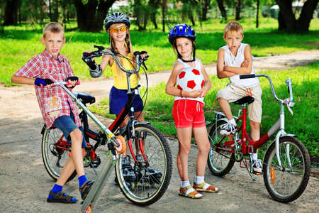 bicycling: Group of active children in a summer park. Stock Photo