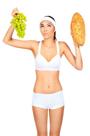 Portrait of a beautiful young woman making choice between loaf and grapes. Isolated over white background. photo