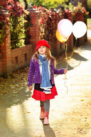 play the old park: Shot of a cute girl walking with balloons at the park.