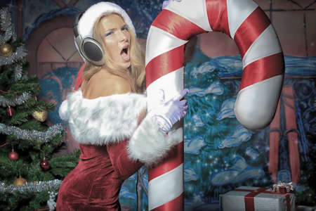 Beautiful young woman in Santa Claus clothes and headphones over Christmas background. Stock Photo - 10978363