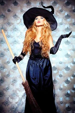 brujas sexis: Casa de la bruja de Halloween con una escoba sobre el fondo de la vendimia. Foto de archivo