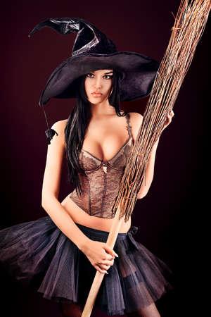 Charming Halloween-Hexe mit Besen auf schwarzem Hintergrund. Standard-Bild